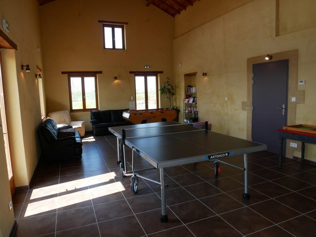 Une grande salle de jeux avec ping-pong et baby-foot
